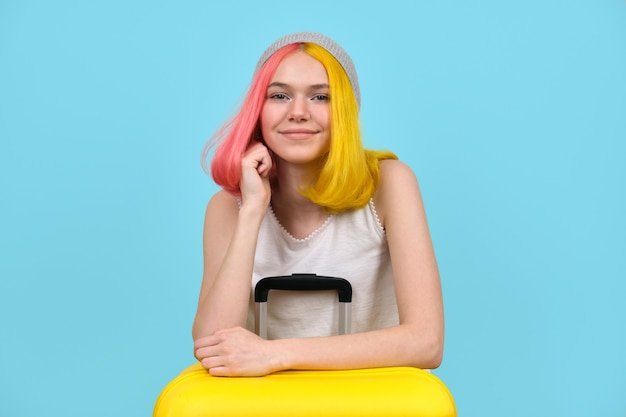 Giovane donna con la valigia gialla, sorridente ragazza adolescente hipster con i capelli tinti, guardando la fotocamera. sfondo blu studio. turismo, viaggi, stile di vita, studenti, concetto in movimento Foto Premium