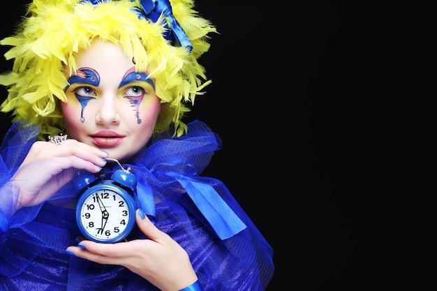 Giovane donna con la parrucca gialla piuma. tema delle vacanze.