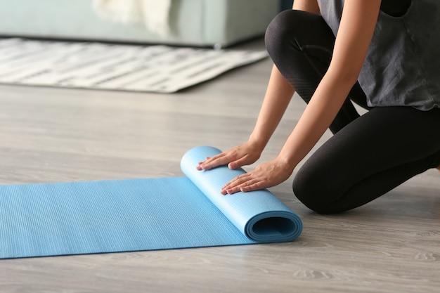 Giovane donna con materassino yoga al chiuso