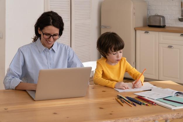 La giovane donna lavora al computer portatile e al figlio disegna