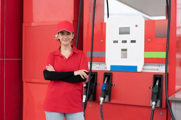 Giovane lavoratrice in uniforme rossa in piedi traverse pronte per il servizio con l'ugello della pompa del carburante alla stazione di servizio
