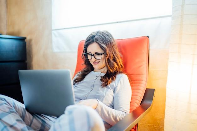 Giovane donna che lavora dal letto a casa con il computer.