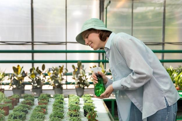 Giovane donna che lavora in una serra