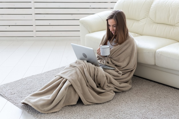 Giovane donna che lavora a casa in plaid, bevendo tè e chiacchierando