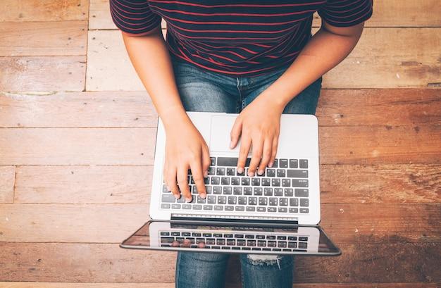 Giovane donna che lavora al computer portatile mentre sedendosi sul sofà rosso in salone a casa, lavorando dal concetto domestico fondo di concetto di affari.