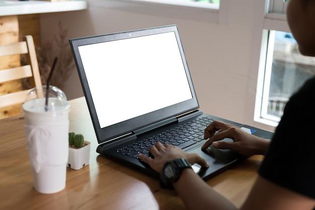 Computer portatile di lavoro della giovane donna sullo scrittorio di legno