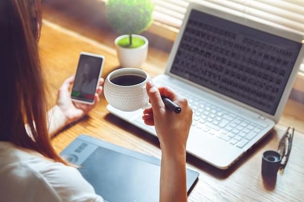 Giovane donna che lavora al computer portatile utilizzando tavoletta grafica