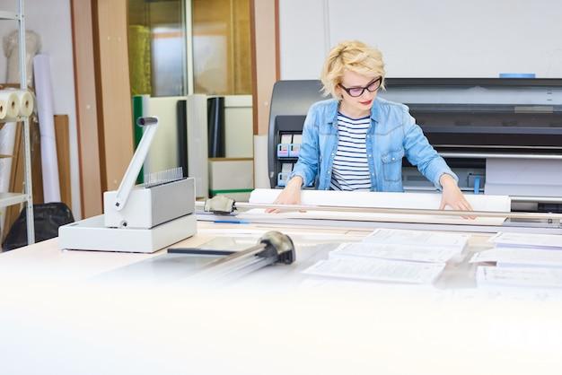 Giovane donna che lavora in tipografia