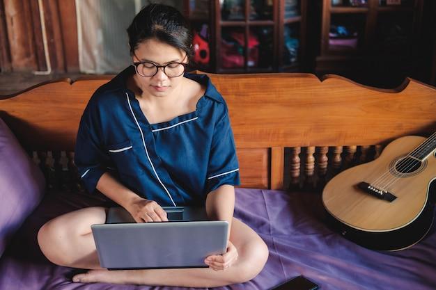 Seduta di lavoro della giovane donna sullo strato con il computer portatile a casa