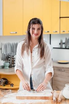 Giovane donna che lavora con la pasta in cucina