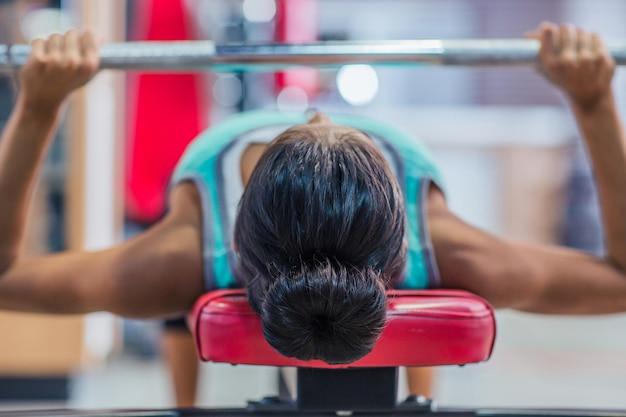 Giovane donna allenamento con bilanciere in panchina in palestra
