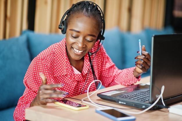 La giovane donna lavora in un operatore di call center e un agente del servizio clienti che indossa cuffie con microfono che lavorano su laptop