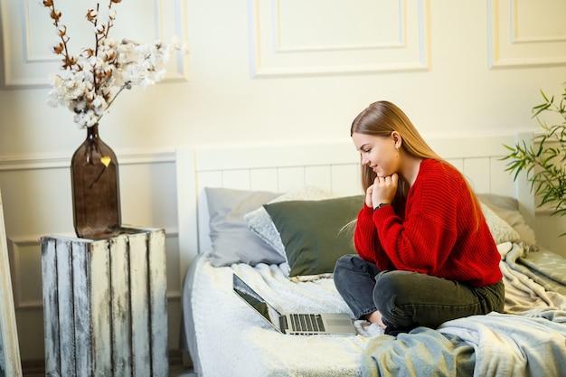 La giovane donna lavora al computer, seduta su un letto, lavorando a distanza. una ragazza con i capelli lunghi in un maglione rosso e jeans lavora a casa.