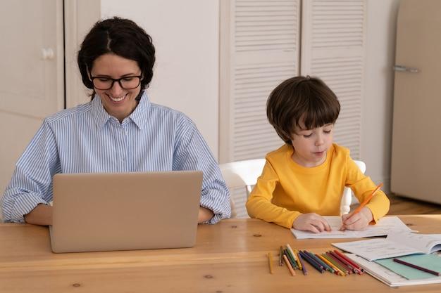 La giovane donna lavora al computer portatile mentre il figlio disegna