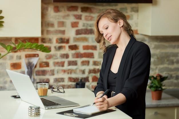 Una giovane donna lavora a distanza nella sua cucina. un capo femmina che fa appunti su un quaderno mentre i suoi impiegati si occupano di una videoconferenza a casa.