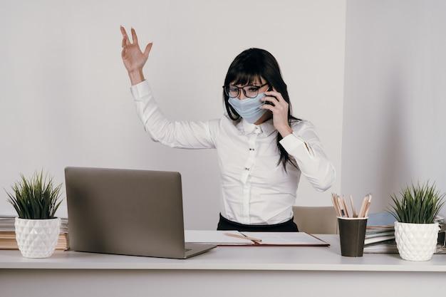 Una giovane donna lavora a distanza in ufficio con una maschera protettiva durante un'epidemia