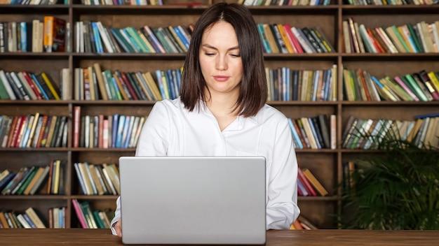 La giovane donna lavora con le carte dal computer portatile al tavolo in biblioteca