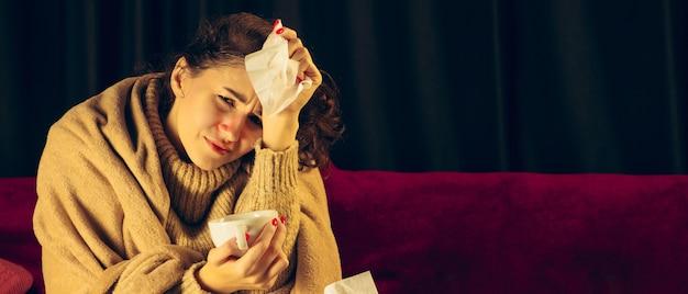 La giovane donna avvolta in un plaid sembra malata, malata, starnutisce e tossisce seduta sul divano di casa al chiuso. sanità e medicina, prevenzione delle malattie, sintomi di malattie stagionali e autotutela. volantino