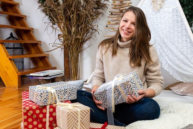 Giovane donna che confeziona i regali a casa, confezionando i regali per natale