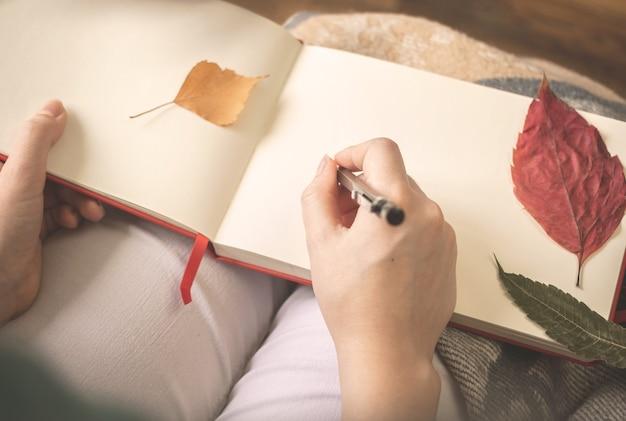 La giovane donna scrive al suo vecchio diario con foglie d'autunno. accogliente foto di sfondo autunnale