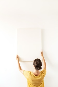 Giovane donna in camicetta gialla tenere tela bianca con spazio vuoto copia mockup. il minimo concetto di arte.