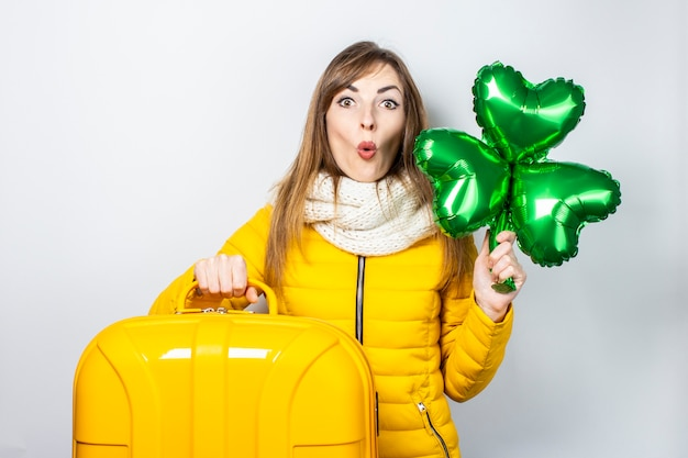 Giovane donna in un piumino giallo e un cappello isolato