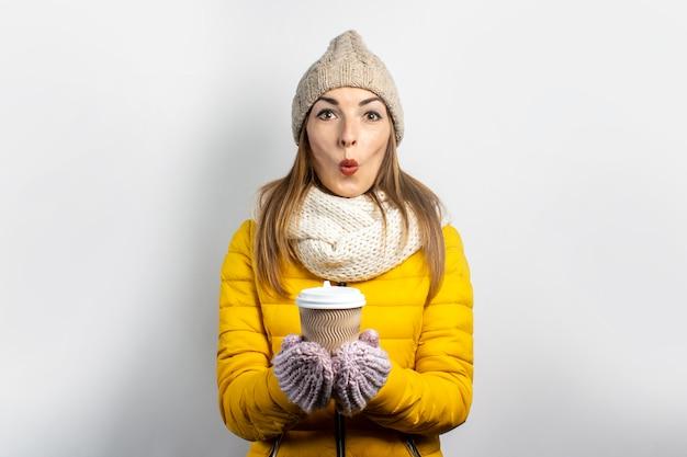 La giovane donna in una giacca gialla e un cappello tiene un bicchiere di caffè o tè