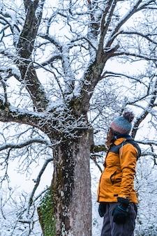 Una giovane donna con una giacca gialla in un albero innevato su una strada ghiacciata. neve nella città di opakua vicino a vitoria in araba