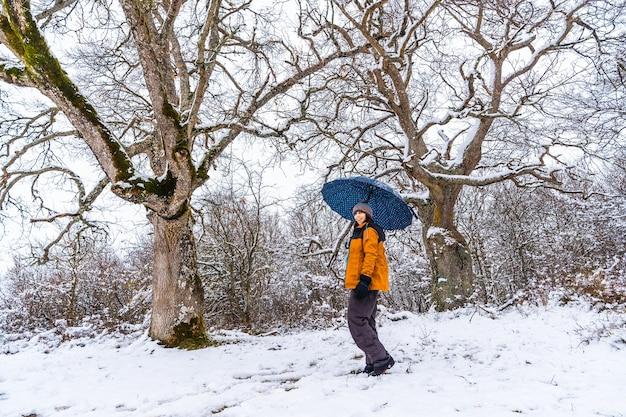 Una giovane donna con una giacca gialla e un ombrello che gioca con la neve su un ramo di un albero. neve nella città di opakua vicino a vitoria