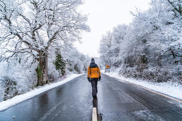 Una giovane donna con una giacca gialla che cammina lungo una strada ghiacciata e nega alberi. neve nella città di opakua vicino a vitoria in araba