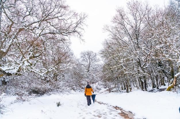 Una giovane donna con una giacca gialla che cammina lungo il sentiero di alberi congelati. neve nella città di opakua vicino a vitoria in araba