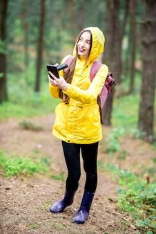 Giovane donna in impermeabile giallo utilizzando smart phone per l'orientamento durante la passeggiata nella verde pineta