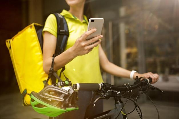Giovane donna in camicia gialla che consegna cibo usando gadget per tenere traccia dell'ordine nella strada della città. corriere che utilizza l'app online per la ricezione del pagamento e il monitoraggio dell'indirizzo di spedizione. tecnologie moderne.
