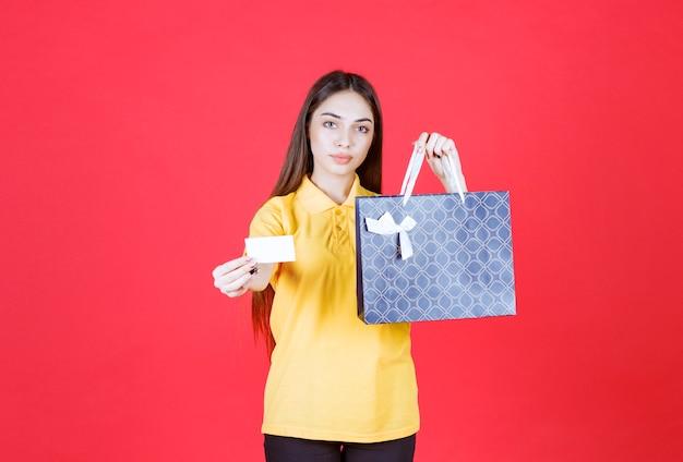 Giovane donna in camicia gialla che tiene una borsa della spesa blu e presenta il suo biglietto da visita
