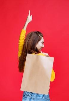 Giovane donna in camicia gialla che tiene una borsa della spesa di cartone