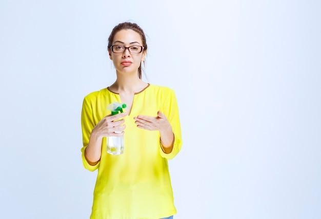 Giovane donna in camicia gialla che tiene uno spray detergente e lo controlla in mano