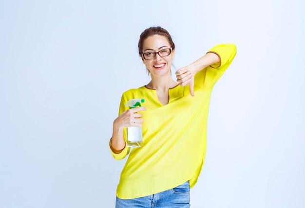 Giovane donna in camicia gialla con in mano uno spray detergente