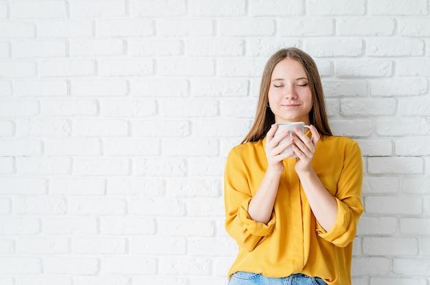 Giovane donna in camicia gialla che tiene una tazza con sfondo di mattoni bianchi