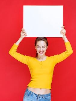 Giovane donna in camicia gialla con in mano un pannello informativo quadrato