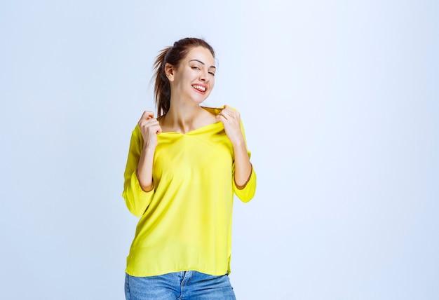 Giovane donna in camicia gialla che indica se stessa