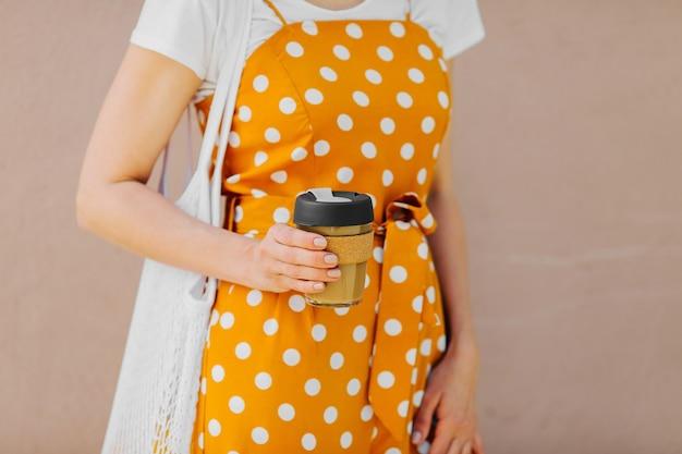 La giovane donna in vestiti gialli di estate tiene la tazza da caffè riutilizzabile. stile di vita sostenibile.