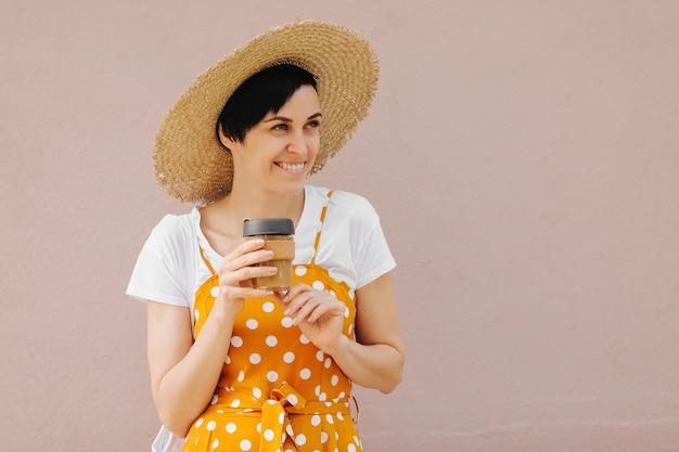 Giovane donna in abiti estivi gialli con una borsa ecologica di frutta e una tazza da caffè riutilizzabile.