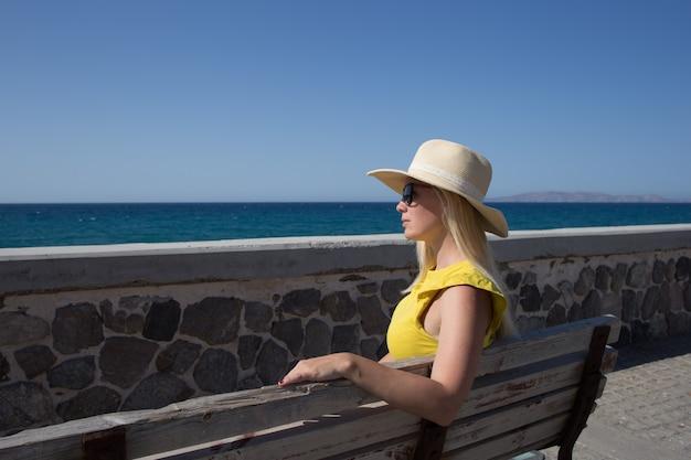 T-shirt gialla e cappello della giovane donna che riposa sul lungomare su una panca di legno.