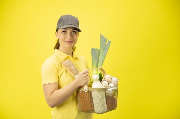 Giovane donna in uniforme gialla che maneggia cesto di cibo, frutta, verdura, latte e uova