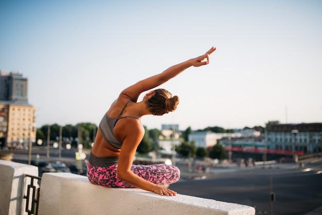 Giovane donna in posa yoga, città
