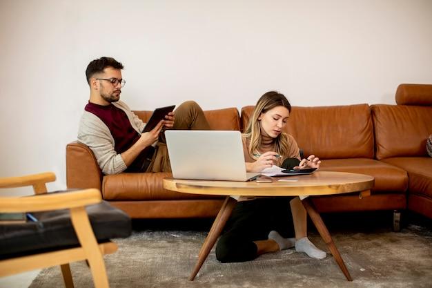 Giovane donna e giovane uomo utilizzando laptop mentre è seduto vicino al divano di casa