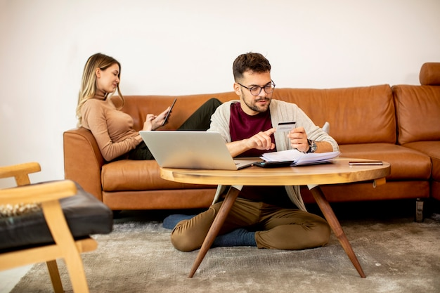 Giovane donna e giovane uomo che utilizza laptop per il pagamento online mentre è seduto accanto al divano di casa