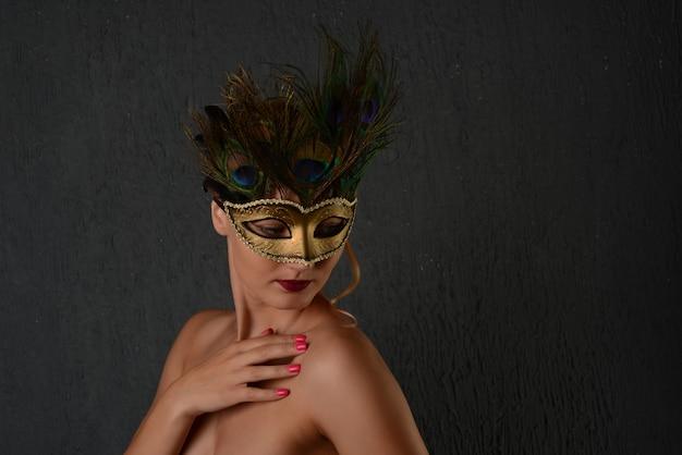 Giovane donna in maschera di carnevale veneziano ritratto femminile in primo piano. sfondo scuro