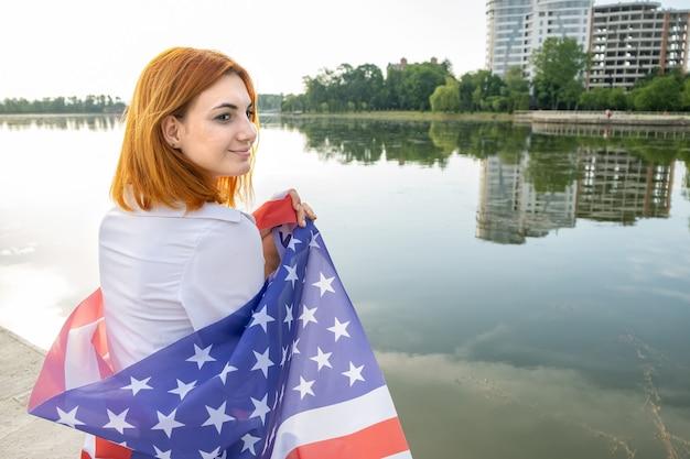 Giovane womanl che tiene la bandiera nazionale usa sulle sue spalle con alti edifici per uffici in una città che celebra il giorno dell'indipendenza degli stati uniti.