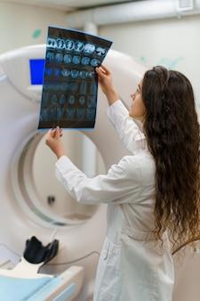 Il medico delle giovani donne in abito medico esamina i risultati accanto allo scanner ct
